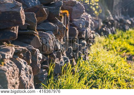 An Uneven Stonewall On The Countryside Beside A Grass Path