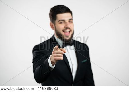 Charming Man In Tuxedo Points Index Finger Into Camera Lens And Winks, Flirts. Hey, You. Gentleman W