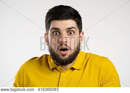 Frightened Man Afraid Of Something And Looks Into Camera With Big Eyes Full Of Horror Over White Wal