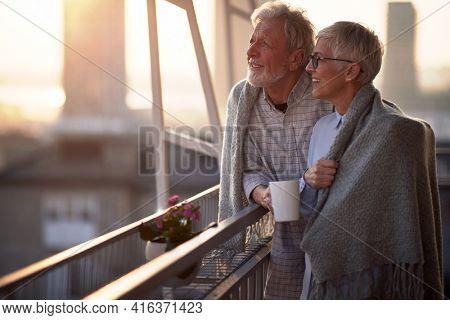 Happy senior couple enjoying morning coffee together on the balcony