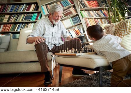 Happy grandpa and grandson playing chess together at home