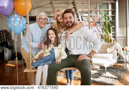 Happy family portrait with grandmother at home; Happy family offspring concept