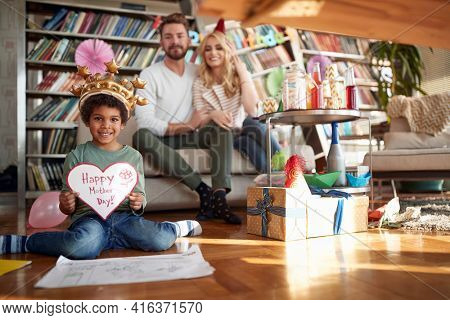 Cheerful caucasian couple with adopted afro american child celebrating mother's day together