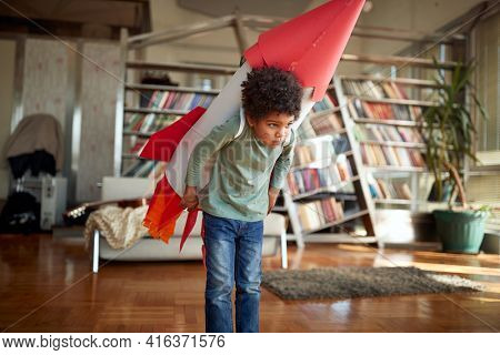 Cute afro american boy playing with paper rocket at home