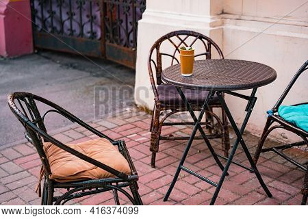 Brown Wicker Chairs And Round Plastic Table Stands On The Sidewalk Near A Cafe In The Building. City