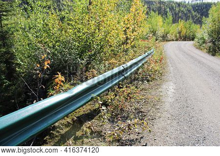 A Protection Rail On The Side Of A Gravel Road