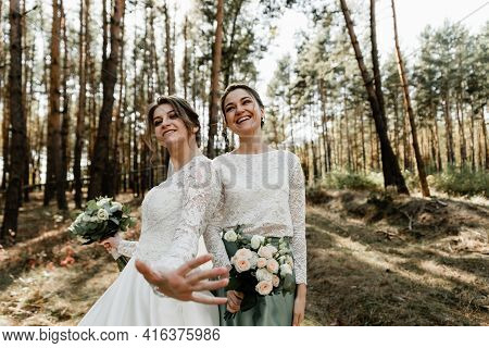 The Bride And Her Friend Are Dressed In Wedding Dresses Are Having Fun In The Forest Holding Bouquet