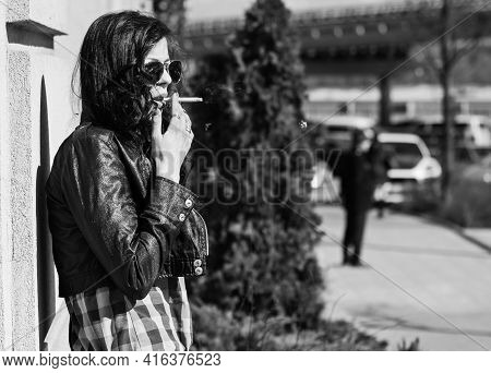 Brunette Woman With Blue Shirt And Jeans Smoking In City