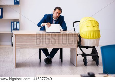 Young male employee looking after kid at workplace