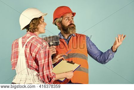 Discussing Renovation With Contractor. Price List. Couple Look Documents. Woman And Man Safety Hard