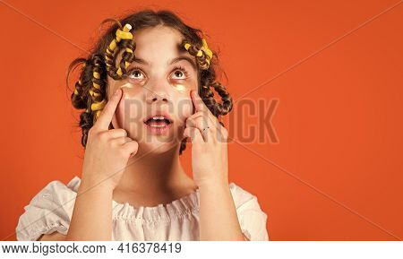 Little Happy Girl With Curlers In Hair. Fabric Mask Under Eyes For Beauty. Cute Kid Standing With Pa