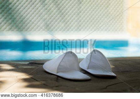 White Cloth Carpet Sippers Placed On The Side Of A Out Of Focus Pool With Light Reflections Playing
