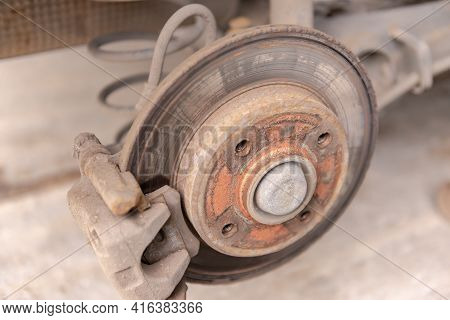 Heavily Worn Brake Disc. Car Brake Disc After Removing The Wheel. A Rusty Disk That Needs To Be Repl