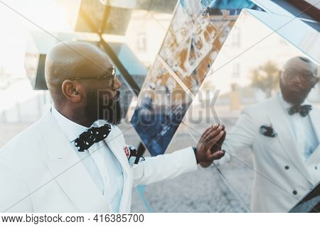 A Profile Portrait Of A Dapper Handsome Bald Bearded Mature Black Man In A White Costume With A Dott