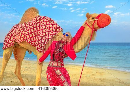 Happy Blonde Woman With Camel On A Sand Beach Of Khor Al Udaid In Persian Gulf Of Southern Qatar. Ca