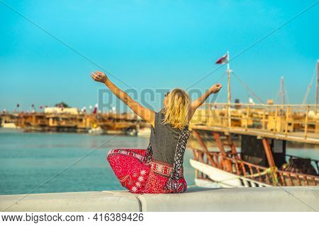 Tourism In Qatar. Blonde Caucasian Woman With Open Arms At Corniche Promenade With Dhow Harbour On B