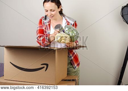 July 15, 2020. Bologna, Italy. Unpacking The Parcel Amazon. The Woman Opens The Box And Happily Take