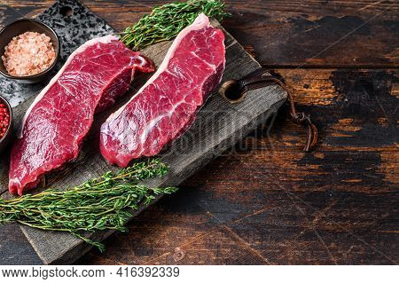 Raw Sirloin Beef Meat Steak On A Wooden Cutting Board With Herbs. Dark Wooden Background. Top View.