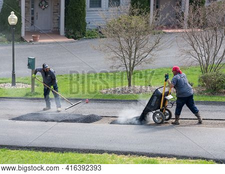 Morgantown, Wv - 7 April 2021: Workers Applying A Layer Of Tarmac Or Extra Blacktop To Repair Damage