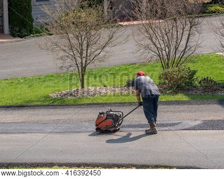 Worker Compacting A Layer Of Tarmac Or Extra Blacktop To Repair Damage To Asphalt Street With A Plat