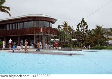 Yeppoon, Queensland, Australia - April 2021: People Swimming In Public Infinity Pool Watched Over By