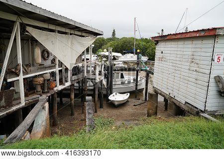 Yeppoon, Queensland, Australia - April 2021: Boats Moored Between Dilapidated Shacks At Old Timber J