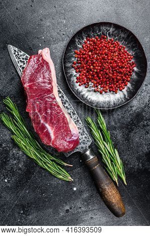 Raw Marbled Beef Meat Strip Loin Steak On A Knife. Black Background. Top View