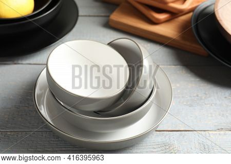 Set Of Clean Dishware On Grey Wooden Table