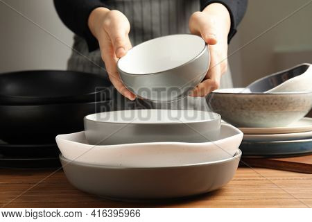 Woman Holding Bowl Over Clean Dishware, Closeup