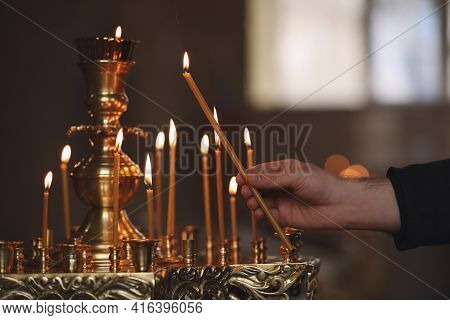 Man Lighting Candle Near Stand In Church, Closeup. Baptism Ceremony