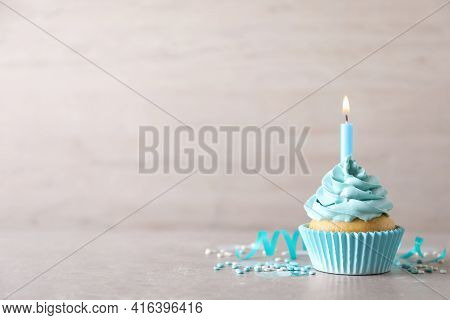 Delicious Birthday Cupcake With Burning Candle, Sprinkles And Streamer On Grey Table, Space For Text