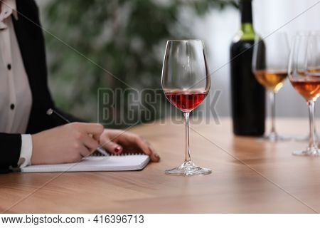 Sommelier Making Notes During Wine Tasting At Table Indoors, Closeup