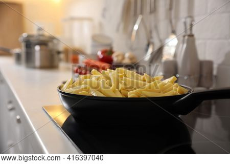 Frying Pan With Cut Raw Potatoes On Cooktop
