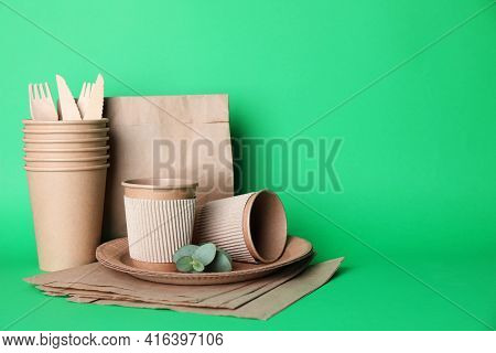 Set Of Disposable Eco Friendly Dishware On Green Background