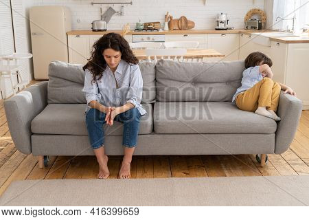 Pensive Young Mommy Sit On Couch With Son Offended With Family Fight And Moms Scolding. Disobedient