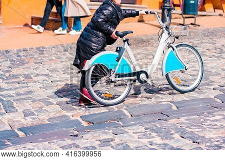 Unrecognizable Woman In Black Jacket Pushing A Sharing Bike On A Broad Cobblestone Hill In The Histo