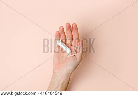 Woman Hand Holding Medical Female Tampons On Beige Background. Hygienic White Organic Tampon For Wom