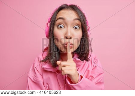 Surprised Asian Woman Looks With Mysterious Expression Tells To Be Quiet Makes Taboo Gesture Listens