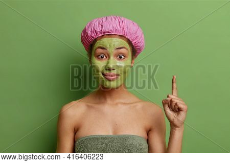 Surprised Cheerful Dark Skinned Woman Applies Green Nourishining Mask Indicates Above Demonstrated C
