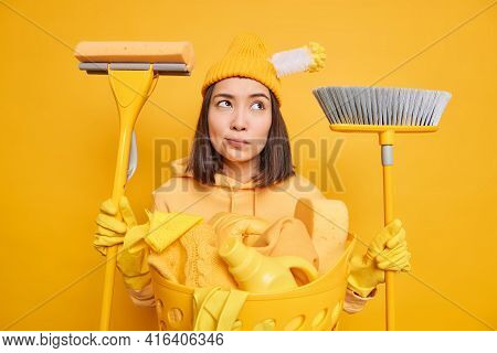 Tired Thoughtful Asian Woman Does Laundry At Home Holds Cleaning Tools Busy With Cleanup Going To Sw