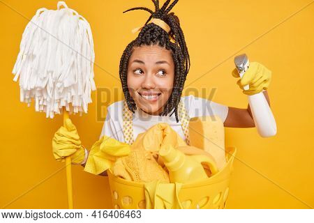 Homework And Cleaning Concept. Happy Dreamy Woman With Dreadlocks Holds Mop And Detergent Concentrat