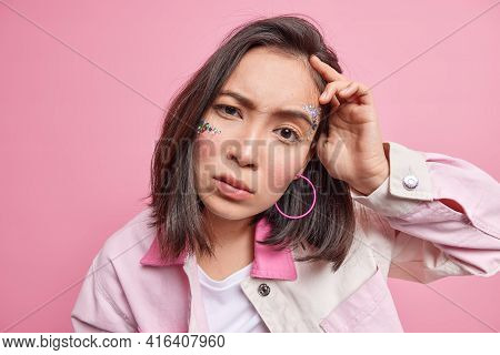 Close Up Portrait Of Serious Good Looking Brunette Asian Woman Looks Scrupulously At Camera Has Atte
