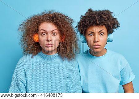 Studio Shot Of Surprised Serious Mixed Race Women Gaze Puzzled At Camera Listen Music Via Wireless H