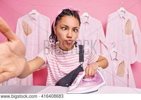 Dark Skinned Ethnic Woman With Dreadlocks Makes Funny Grimace Poses For Selfie Irons Clothes For Fam