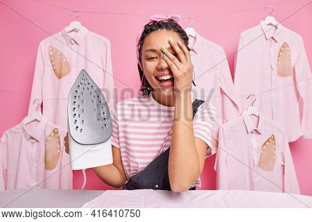 Joyful Housewife Makes Face Palm Smiles Happily Busy Ironing Clothesat Home Poses Near Board Holds E