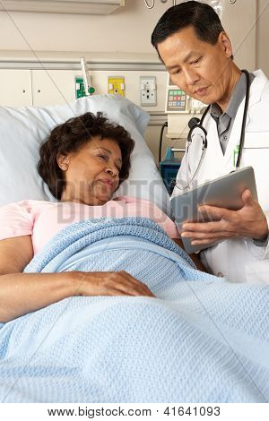 Doctor Using Digital Tablet Talking With Senior Patient poster