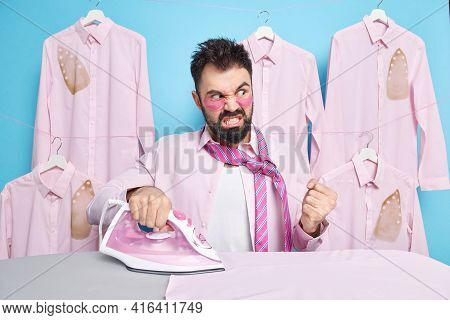 Middle Aged Angry Bearded Man Clenches Fist With Annoyance Being Tired Of Ironing And Doing Domestic