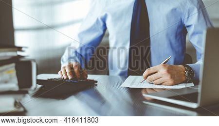 Unknown Man Accountant In Blue Shirt Use Calculator And Computer With Holding Pen On While Staying A