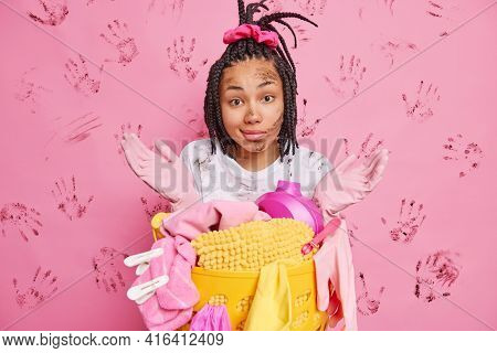 Hesitant Housewife Spreads Palms And Looks Confused Poses Near Laundry Basket Being Dirty After Wash