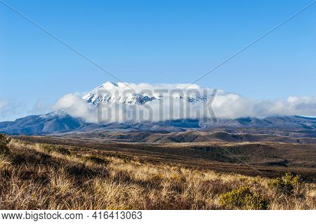 Beautiful landscape of the New Zealand - a mighty volcano Mt. Ruapehu covered by snow is hidden in clouds. New Zealand